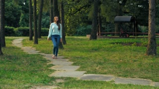 Young brunette girl with long hair in bright sandals is on a path in a park and glances up at the trees and the sun