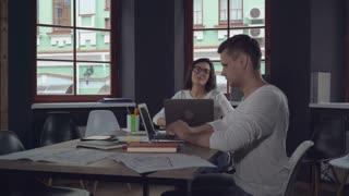 Young caucasian woman and handsome man working in the casual office. Smiling businesswoman relaxing after hard focused working