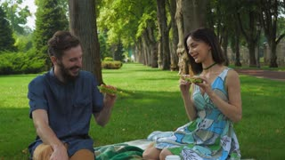 Young couple boy and girl in a summer picnic at the park holding sandwich