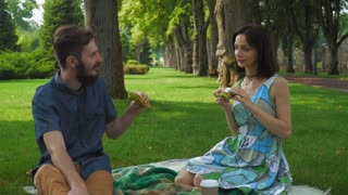 Young couple, guy with the girl eat sandwiches with salad on a picnic. Communicate, rejoice