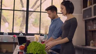 young couple in love cooking on the kitchen. Handsome man talking with attractive woman and using laptop. People speaking and smiling enjoy day at home. Family fix dinner and drinking red with. On the