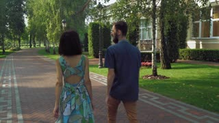 Young couple near the track is in a beautiful old park. They talk and smile