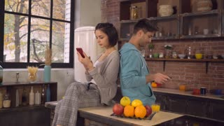 Young couple using gadgets in kitchen at home. Caucasian woman texting message on smartphone. Man holding touch screen tablet surfing internet or check mail wearing in hoodie. Relationships in family