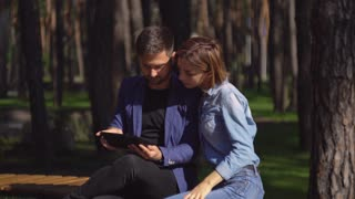 Young family watching some funny video in touch screen tablet in park. Casual happy man and woman enjoy sunny day outdoors