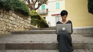 Young female checks mail on the laptop. Caucasian adult model working with pc outdoor. On the background building windows with closed shutters palm tree and green bushes