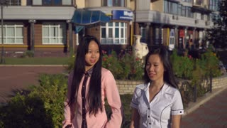 Young friends walking on the street. On the background urban view with buildings, shops, cafe. Two women talking and walking on the pavement. Asian girls wearing in casual shirts at sunny day