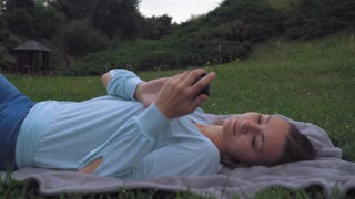 Young girl brunette lying on blankets on the lawn in the park, summer, gaining a message on your phone, then closes her eyes and enjoying the holiday. Falls asleep