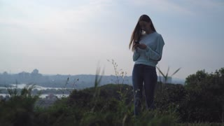 Young girl with long hair, which the wind driveth in green blouse stands on a hill and looking at your phone