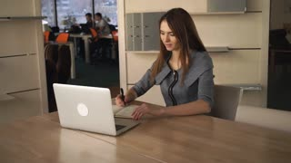 Young happy woman sitting at the working place. Wearing in elegant grey dress. Redhead caucasian model. Female works at her office