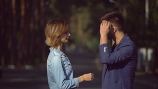 Young man and woman in the city correcting hair each other. Happy pair rejoice to spend time together. Couple in love looking with smile. Attractive girl and handsome man wearing in casual denim shirt
