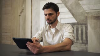 Young man using touch screen tablet at home with creative design wall. Guy wearing in casual shirt scrolling documents on modern device or looking on the pictures or surfing the internet. He looks