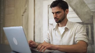 Young professional business man work in the office. Sitting in the room with creative interior on the wall. Concentrated engineer computing. Latino guy typing on the modern laptop wearing in casual