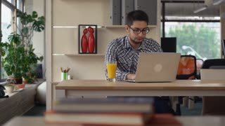 Young professional businessman working in the modern spacious office. Casual man using computer typing on keyboard sitting at the working place drinking orange juice. Mixed race worker looking on the