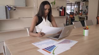 Young professional businesswoman sitting at the working place with casual interior. Mixed race female holding paper document with chart and diagram. On the wooden desk financial or marketing graph