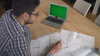 Young professional designer checking architectural sketch at the working place with laptop pencil line equipment for drawing and draftsmanship. On the big desk plan new building or house guy draw some