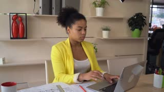 Young professional lady working with computer drinking tea