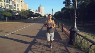 Young sport athletic guy in shorts and a T-shirt runs ahead on a path near the house. Boy sets the camera on the stand. Happy man running i the city near buildings. Urban view. Male listining music on