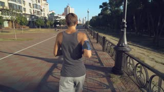Young sport athletic man in shirt and shorts running on a path near the house. guy sets the camera on the stand. Rear back view