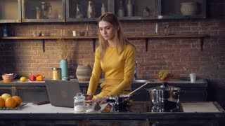 Young woman cooking dinner and reading recipe. Adult lady using internet on pc in the kitchen. Caucasian model sitting near cooker looking on the laptop screen. Happy girl typing on keyboard in loft