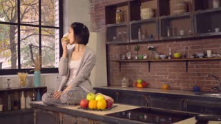 Young woman enjoy breakfast in the kitchen. Happy girl eating apple. Healthy diet at home