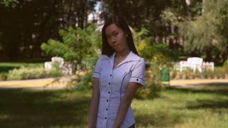 Young woman flirtatiously smile at the camera. Asian student standing in front of green tree. Embarrassed attractive girl smiling. Businesswoman wearing in formal shirt with short sleeves stands in