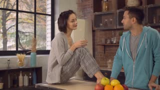 Young woman holding glass with water sitting on the table talking with boyfriend. Happy family enjoy conversation in the morning at home. Adult man in hoodie looking on his girlfriend with love