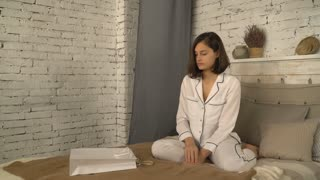 Young woman looks at purchases sitting on bed. Happy smiling lady opening white paper bag gets out clothes. Caucasian model wearing in white pajamas at home. adult girl enjoy purchases or present