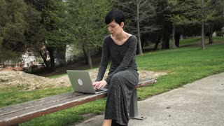 Young woman sitting on the bench in sunny spring day. Adult female typing on the laptop dress in elegant dress. She works outdoor