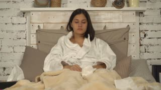 Young woman with common cold lying in bed at home. Lady with rheum ill in flat. Female catch a chill feel bad and unhappy