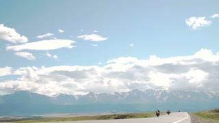 A man rides a motorcycle down a mountain road circa