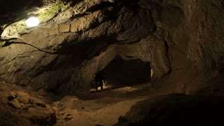 A young man is standing inside a rock cave