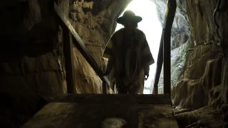 A young woman is standing inside a rock cave