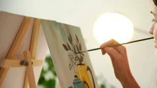 Artist paints a picture of oil paint brush in hand with palette close up. 4k 20s