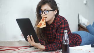 Asian woman eating pizza and looking at digital tablet computer at home