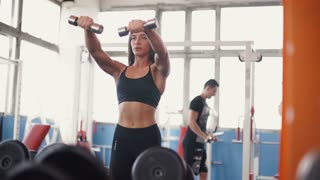 Athletic fitness woman pumping up muscles with dumbbells