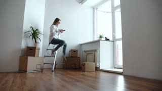 Attractive young woman is moving, standing among cardboard boxes, using a smartphone and smiling
