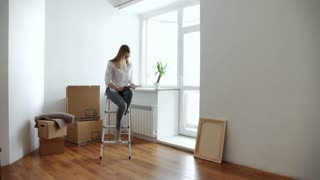 Attractive young woman is moving, standing among cardboard boxes, using a tablet and smiling