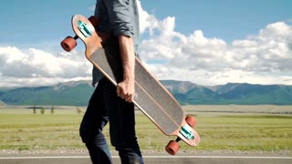 Bearded tattooed man in a red shirt posing with a longboard.