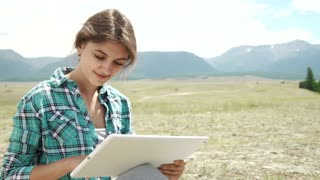 Beautiful brown girl, in a wasteland, using a tablet pc