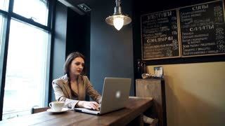 Beautiful hipster woman using laptop at cafe