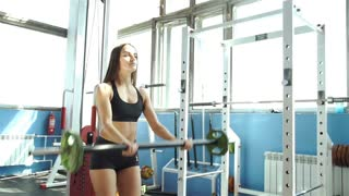 Beautiful woman in a private gym lifting weights in a focussed and serious manner 20s. 1080p Slow Motion