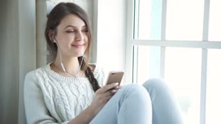 Beautiful young girl sitting at home near a window with a smile looking at phone