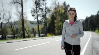 Beautiful young woman runner athlete insert her earphones during training