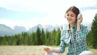 Beautiful Young Woman with Headphones Outdoors. Enjoying Music.