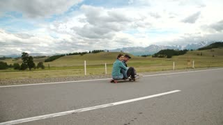 Best friends having fun with skateboard on open road. Young man and woman longboarding together on a sunny day.