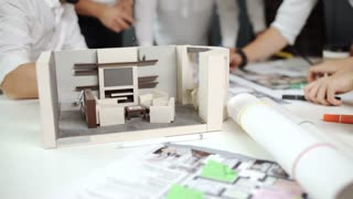 business people group on meeting and presentation in bright modern office with construction engineer architect and worker looking building model and blueprint plans 20s 4k.