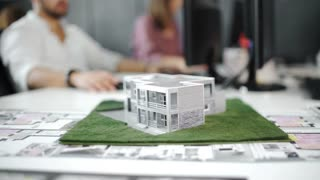 Businessman signs contract behind home architectural model. Close up. 4k