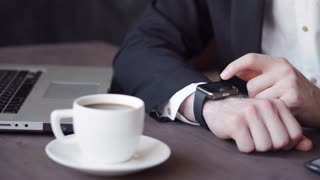 Businessman uses smart watch and phone. Smartwatch concept