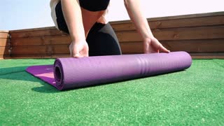 Close-up of young woman unfolding mat for yoga practice. 1080p Slow Motion.