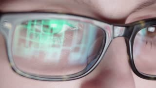 Closeup shot of boy in glasses surfing internet at night